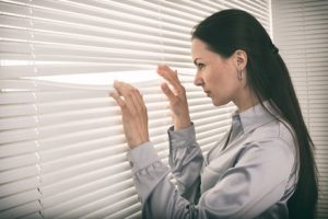 Woman peering out through a blind